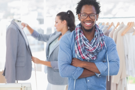black male: Fashion designer posing while his colleague is measuring blazer lapel behind