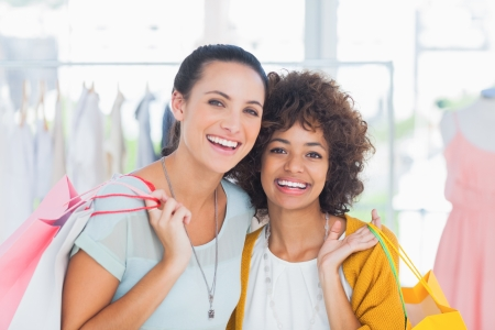 Smiling friends holding shopping bags and smiling at camera Stock Photo - 20638723
