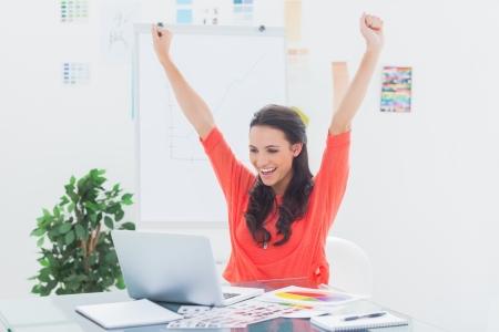 dolgozó: Izgatott nő emelése a karját, miközben dolgozik rajta laptop az irodájában