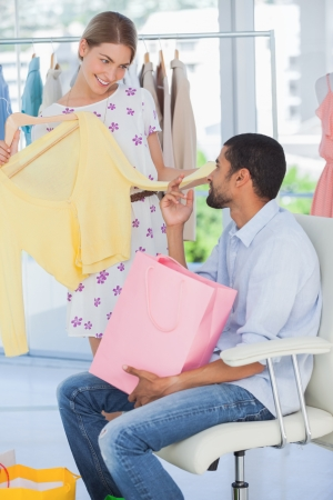 Woman showing clothes to her boyfriend who is sitting in a boutique photo