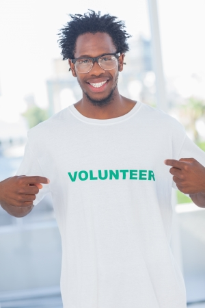 volunteer point: Cheerful man pointing to his volunteer tshirt in a modern office