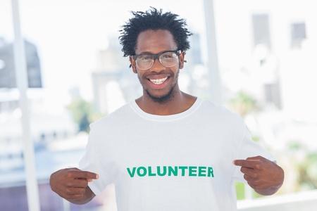 altruismo: Hombre hermoso que se�ala a su camiseta de voluntario en una oficina moderna