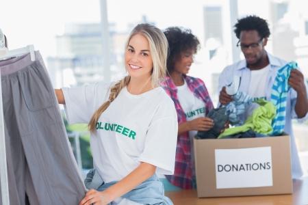 altruismo: Voluntarios alegres poniendo ropa en barra de colgar en su oficina