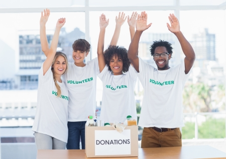 volunteerism: Volunteers raising their arms in front of food in a donation box