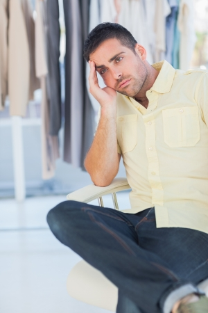 Bored man sitting in a clothing store and holding his head photo
