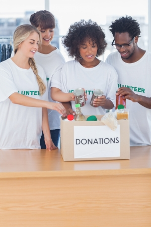 Volunteers putting food in donation box in their office photo