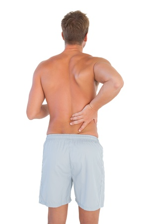 Man with shorts suffering from back pain on white background photo