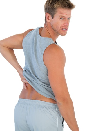 Muscled man grimacing because of a back pain on white background photo