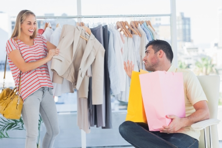 Depressed man looking at his shopaholic girlfriend in a clothing store photo