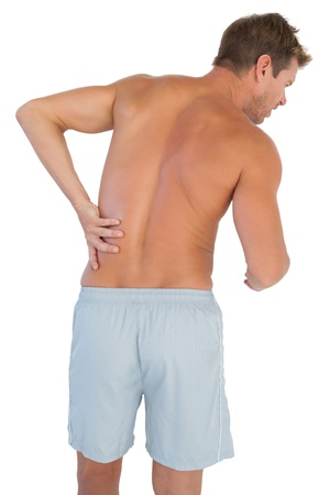 Man with shorts suffering from lower back pain on white background photo