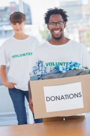 Handsome man holding donation box full of clothes next to a colleague photo