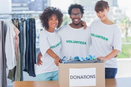 altruismo: Los voluntarios que se unen en su oficina en frente de la caja de donaciones