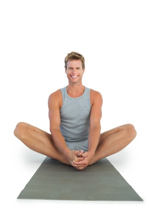Handsome man sitting in lotus position on white background photo
