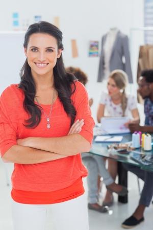 trabajo en oficina: Diseñador de moda bonita con los brazos cruzados en la Oficina brillante sonriendo a la cámara Foto de archivo