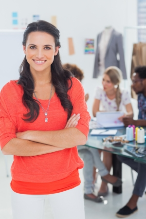 work office: Pretty fashion designer with arms crossed in bright office smiling at camera Stock Photo