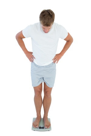 Man looking his weight on a scale on white background photo