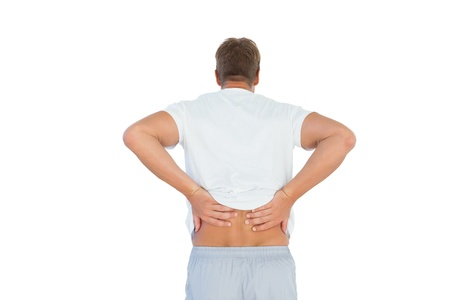 Muscled man suffering from back pain on white background photo