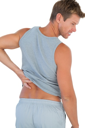 Man grimacing because of a back pain on white background photo