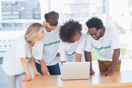 Smiling volunteers working together on a laptop in their office photo