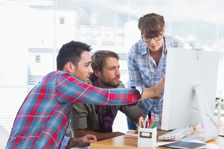casual business team: Team of designers working together on a computer
