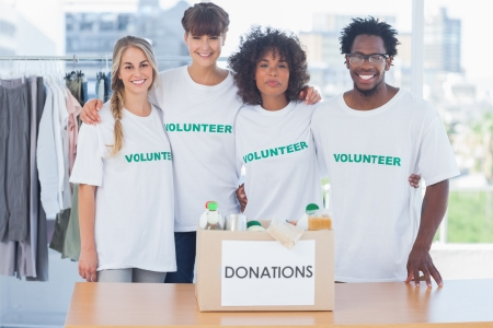 Volunteers standing in front of food in a donation box in their office photo