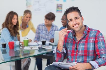 ötletroham: Jóképű tervező ül az irodájában kollégák megbeszélése mögött