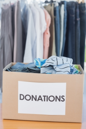 clothes rail: Donations box full of clothes on a table in front of clothes rail