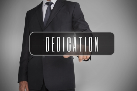dedication: Businessman selecting label with dedication written on it on grey background