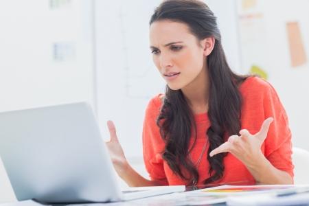 Diseñador Molesto gestos delante de su ordenador portátil en su oficina Foto de archivo - 20637809