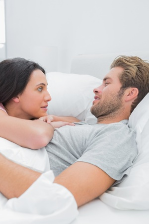 awaking: Cute couple awaking and looking at each other in bed