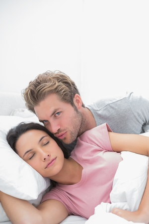 Man kissing his sleeping wife in bed photo