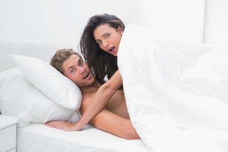 Embarrassed couple surprised in bed  photo