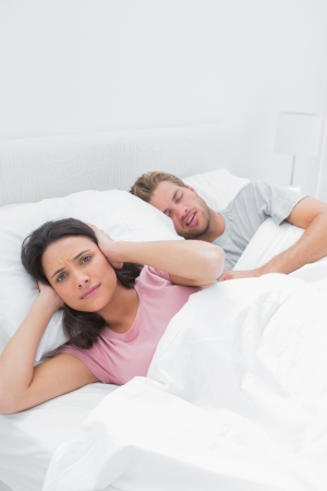 Woman covering her ears while her husband is snoring next to her photo