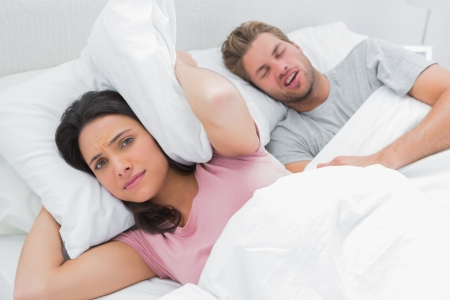 Woman covering ears with pillow while her husband is snoring next to her photo