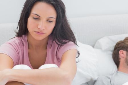 Nadenkende vrouw zat op haar bed naast haar slapende partner Stockfoto