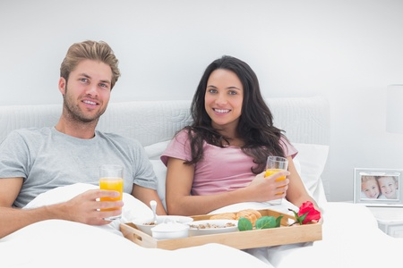 Couple having breakfast in bed with orange juice and cereals photo