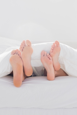 Couple crossing their feet under the duvet in bed photo