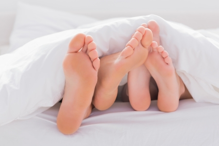 bedding indoors: Couple rubbing their feet together under the duvet in bed