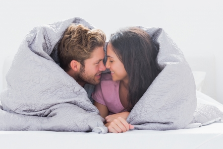 Couple wrapped in the duvet in bed Stock Photo