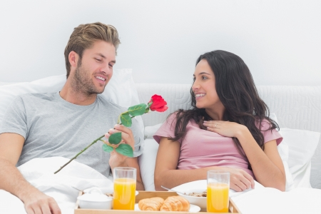Man offering a rose to his wife during breakfast in bed photo
