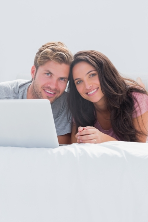 Cheerful couple using a laptop together in bed photo