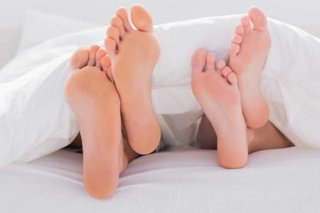 couple au lit: Couples pieds croisés sous la couette dans le lit Banque d'images