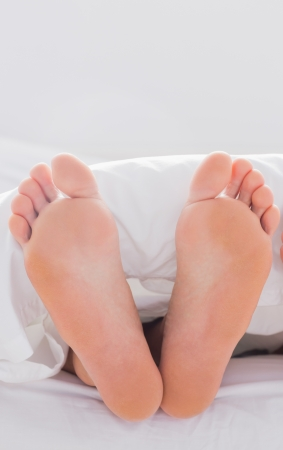 podiatry: Feet sticking out from the quilt in bed Stock Photo
