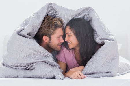 Attractive couple wrapped in the duvet in bed photo