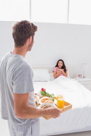 bandejas: Hombre que trae el desayuno a su esposa sorprendida en la cama