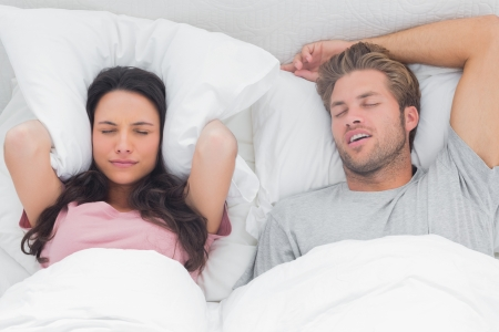 snoring: Woman annoyed by the snoring of her partner in her bed Stock Photo