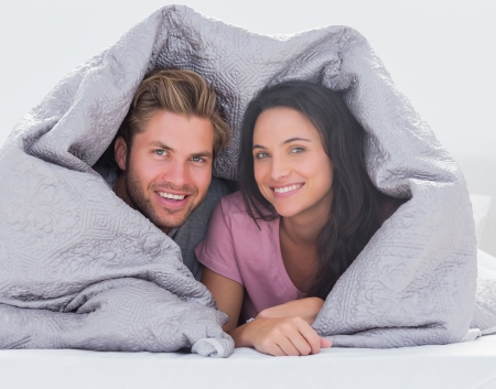 Cheerful couple wrapped in the duvet in bed photo