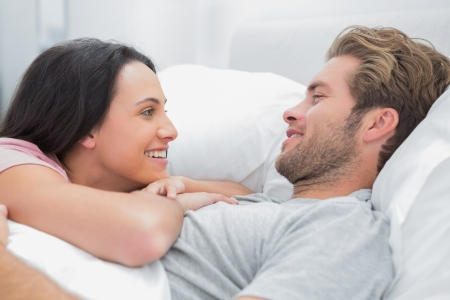 Cheerful couple awaking and looking at each other in bed photo