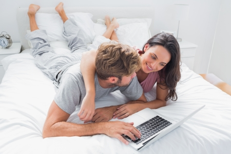 Pretty woman embracing her husband in bed while he is using a laptop photo