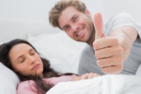 Man giving thumb up while his pretty wife is sleeping photo